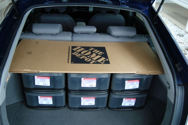 Prius rear cargo area with 6 storage boxes and a folded cardboard box.